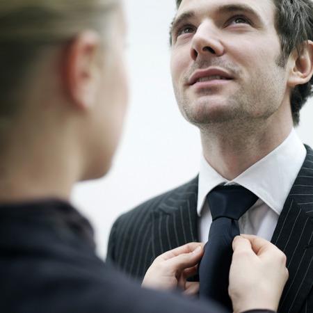 Businesswoman helping businessman with his necktie photo