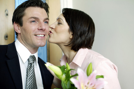 Woman giving her husband a peck on the cheek photo