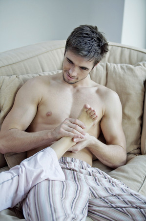 Man massaging his girlfriends foot photo