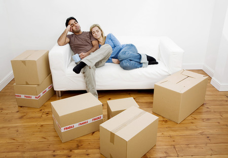 Couple napping on the couch with boxes on the floor photo
