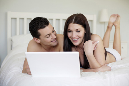 Couple lying forward on the bed using laptop photo