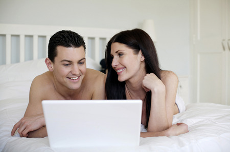 full grown: Couple lying forward on the bed using laptop Stock Photo