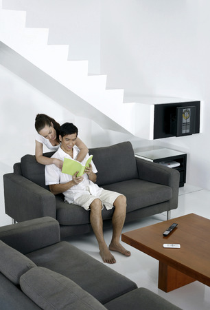 Man reading book with his wife hugging him from the back photo