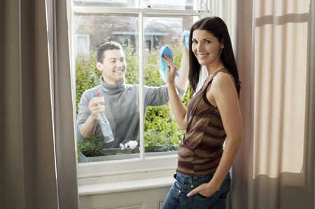 Couple cleaning the window together photo