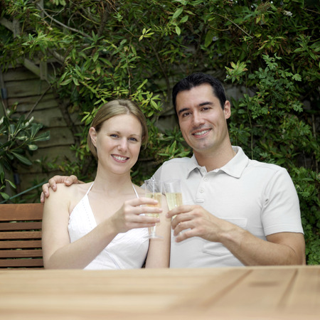 Couple smiling at the camera while holding glasses of champagne photo