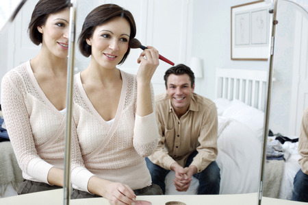 Man watching his wife looking at the mirror applying make-up photo