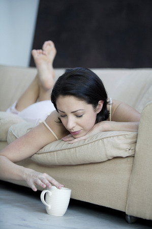 Woman lying forward on the couch holding a cup of coffee photo