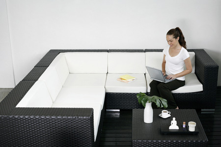 Woman sitting on the couch using laptop photo