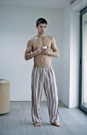 Man in pajamas holding a cup of coffee photo
