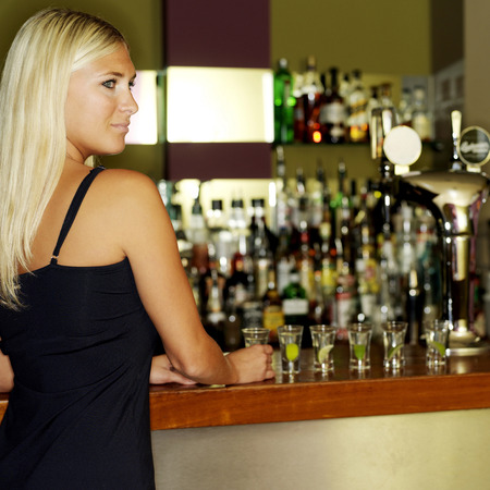 Pretty woman standing in front of a bar counter photo