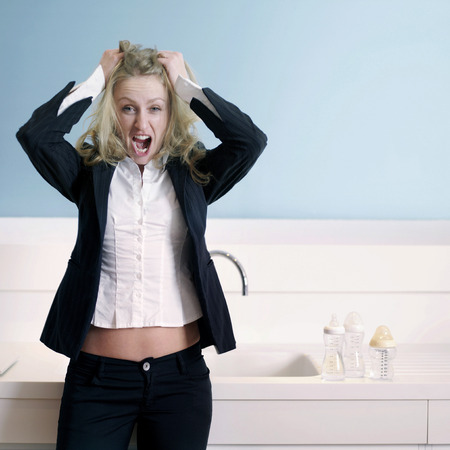 Frustrated businesswoman pulling her hair while screaming photo