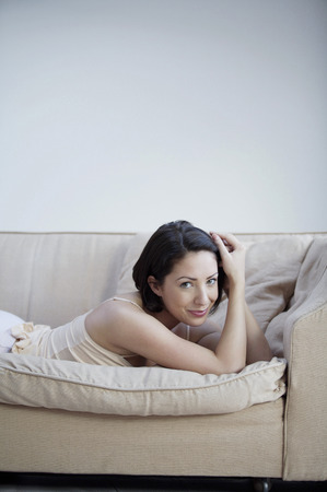 lying forward: Woman lying forward on the couch smiling at the camera