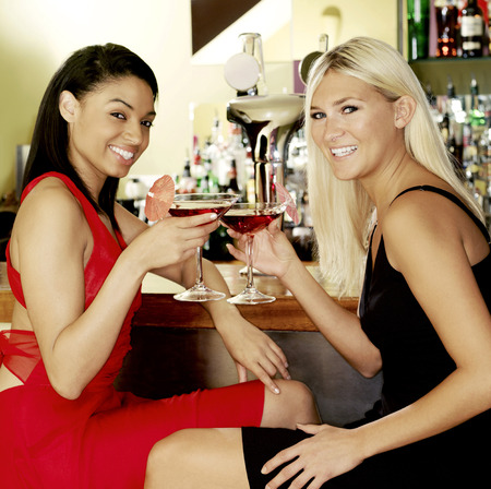 medium length: Two women toasting happily Stock Photo