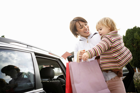 Woman carrying her daughter while holding shopping bags photo
