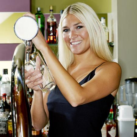 Woman filling up drink at a bar counter photo