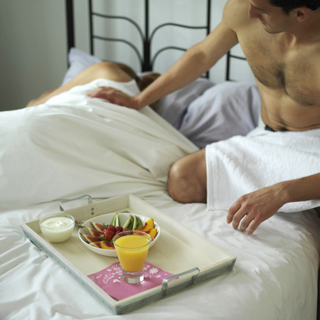Man serving a tray of breakfast for is sleeping wife photo