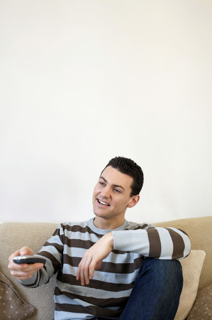 Man sitting on the couch holding television remote control photo