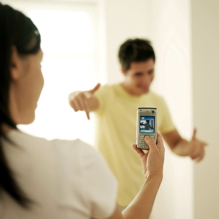 Woman taking her boyfriends picture with a cell phone photo