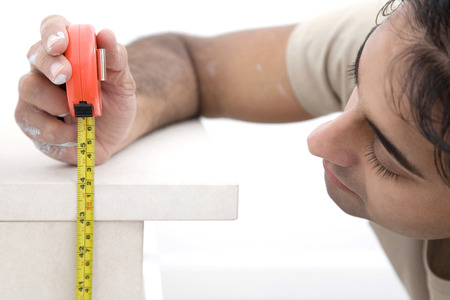 mantelpiece: Man measuring mantelpiece with a tape measure Stock Photo