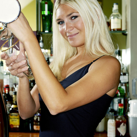 Woman filling up drink at a bar counter photo