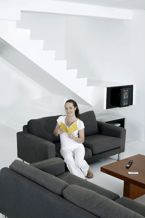 Woman sitting on the couch reading book photo