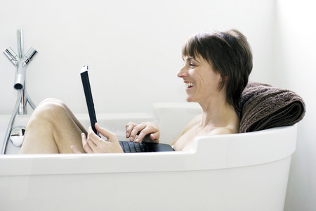 Woman sitting in the bathtub using laptop photo