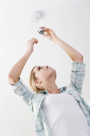 Woman changing the light bulb photo