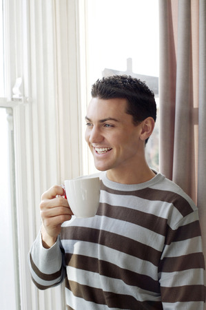 Man holding a cup of coffee while enjoying the view from the window photo