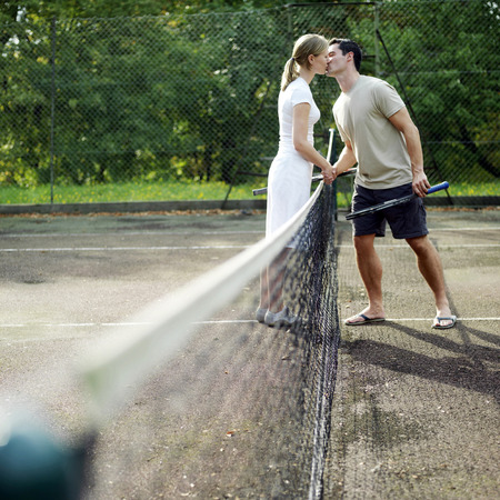 Couple kissing in tennis court photo