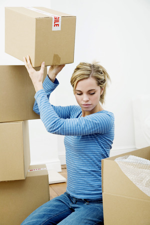 Woman stacking up sealed boxes photo
