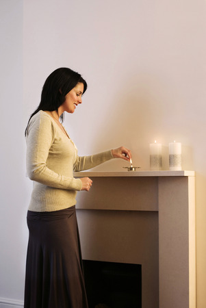 Woman lighting up candles Stock Photo - 26257133