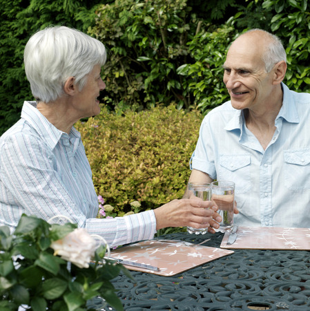 Senior couple resting in the garden, drinking wine photo