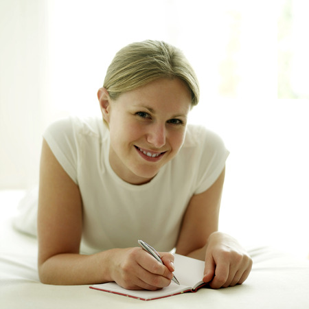 lying forward: Woman lying forward on the bed writing journal Stock Photo