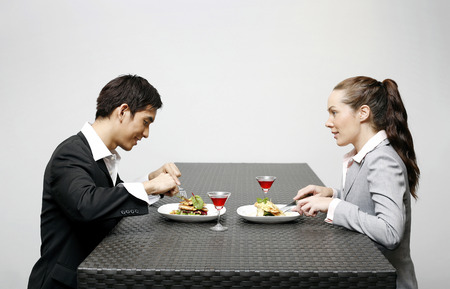 dinner wear: Businessman and businesswoman having dinner together Stock Photo