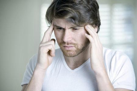 Un hombre que tiene la migraña Foto de archivo - 26257541