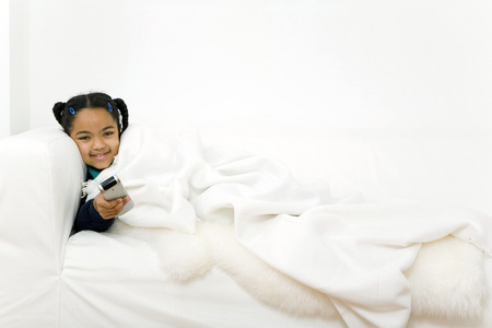 Girl pointing remote control at the camera