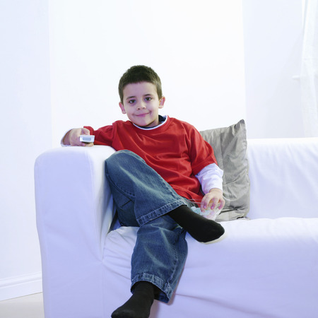 Boy eating candy while watching television photo