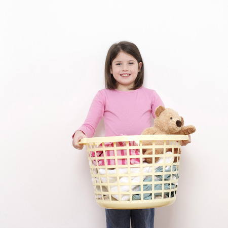 Girl carrying a laundry basket of clothes photo