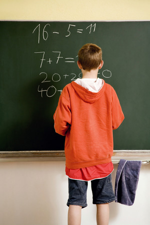 educational problem solving: Boy solving an equation on the blackboard