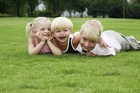 lying forward: Boy and girls lying forward on the field