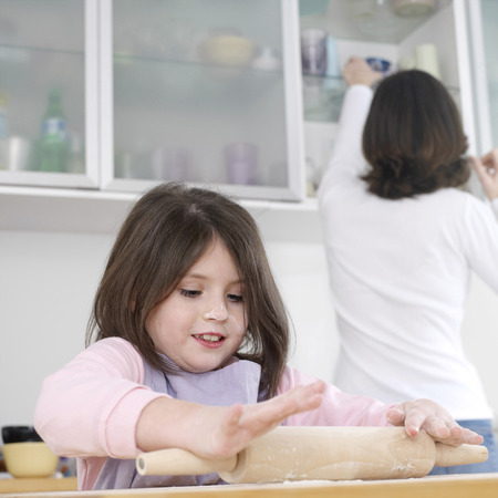 Girl using rolling pin with her mother in the background photo