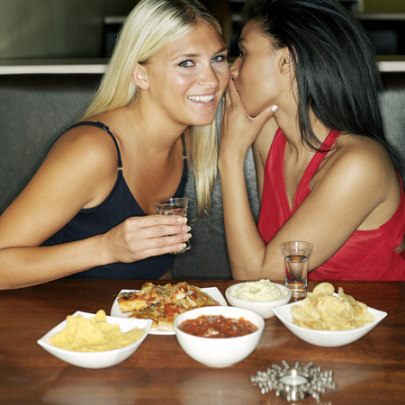 housemate: Two friends sharing secrets Stock Photo