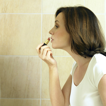 A woman putting on lipstick photo