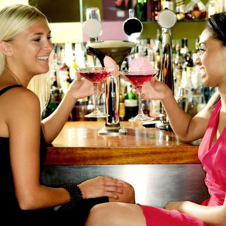 Two women enjoying cocktail in a pub photo