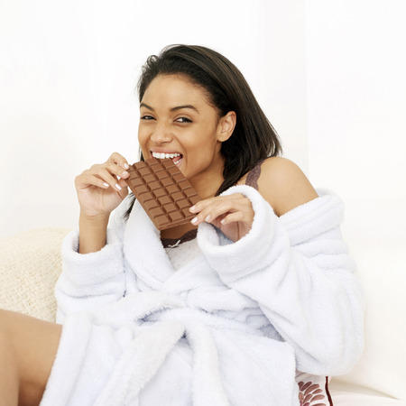 Woman in bathrobe enjoying a bar of chocolate photo