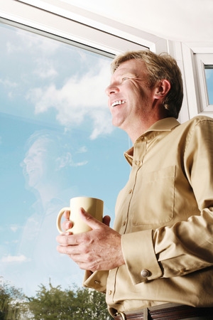 Man holding a cup while looking out of the window photo