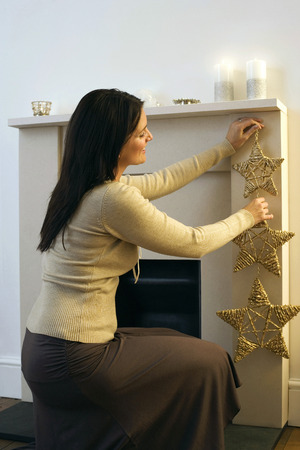 Woman putting up a Christmas ornament Stock Photo - 26258134