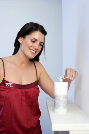 Young lady lighting up a candle Stock Photo - 26258112