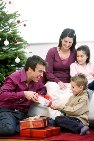 Family gathering around the Christmas tree photo