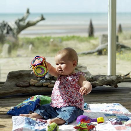 picnic blanket: Ni�a sentada en la manta de picnic a jugar con sus juguetes Foto de archivo